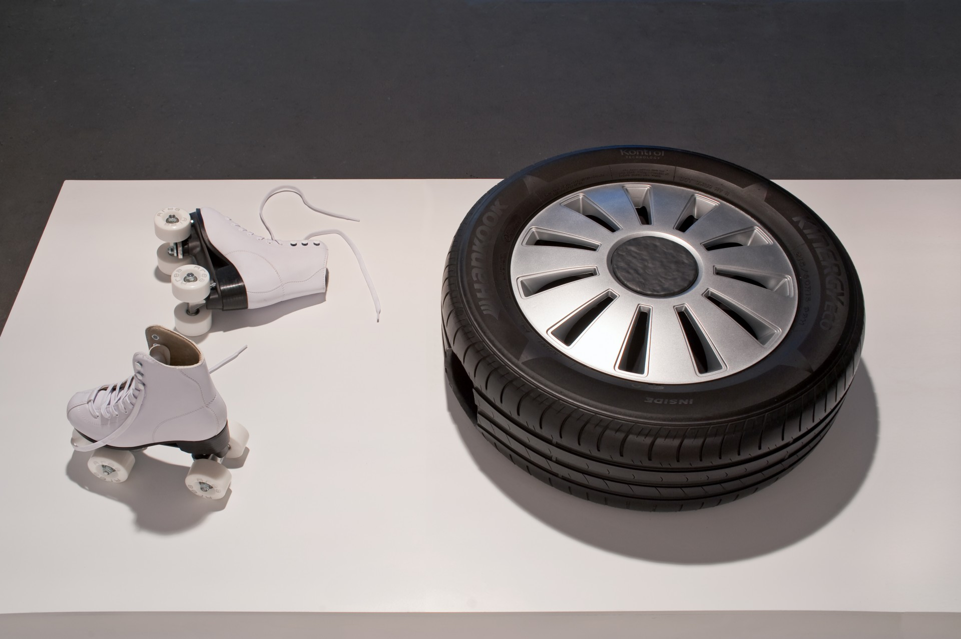 Jamie Isenstein, <i>Wheel on Wheels!</i>, 2017, tire, hubcap, wood, epoxy, roller skates, rotating cast of legs, dimensions variable, performance sculpture. Courtesy of the artist and Gluck50. Ph. Raph Meazza